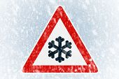 stock photo of slippery-roads  - Snow on an ice covered windshield with warning sign - JPG