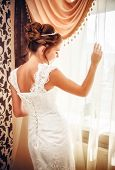 Beautiful bride in white wedding dress standing in her bedroom near the window