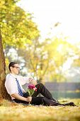 Handsome guy with a bunch of flowers sitting ona  grass and checking the time, in a park