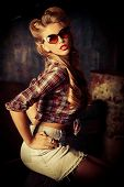Charming pin-up woman with retro hairstyle and make-up in the old garage.