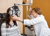 Senior female optometrist examining young woman's eyes in store