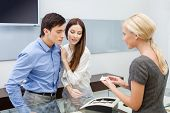 foto of jewel-case  - Shop assistant helps couple to choose jewelry at jeweler - JPG
