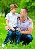 Father keeps son on the knee in the green park. Concept of happy family relations and carefree leisure time