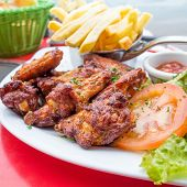 Chicken wings with sauce and golden French fries potatoes