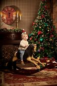 Nice little baby near the Christmas tree. Little boy celebrating Christmas. Cute smiling child with New Year gifts. Christmas Toddler riding a toy horse
