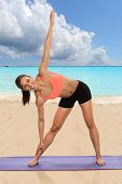Young African American woman practicing yoga on the beach