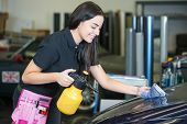 picture of cleaning agents  - Worker cleaning car with cloth and spray bottle in garage or workshop - JPG