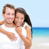 Beach couple lovers on romantic travel in love on honeymoon vacation summer holidays romance. Young happy people, Asian woman and Caucasian man embracing outdoors on tropical beach in casual wear.