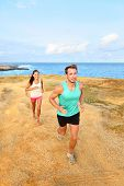 Runners running outside by ocean. Runner couple athletes, man and woman jogging outdoors in beautiful landscape on Green Sand Beach, Papakolea on Big Island, Hawaii, USA.
