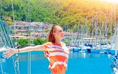 Cheerful female spending summer holidays, smiling woman with raised hands and closed eyes enjoys the