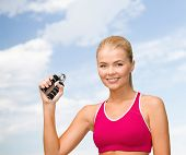 fitness, healthcare and dieting concept - beautiful sporty woman with hand expander
