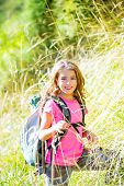 Explorer kid girl walking with backpack between forest grass