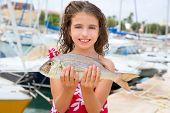 Happy kid fisherwoman with dentex fish catch in Mediterranean marina