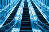 stock photo of escalator  - escalator in blue two tone colors going up stairs in building - JPG
