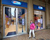 BOLOGNA, ITALY - APRIL 19, 2014: A pedestrian walks past a TIM (Telecom Italia Mobile) retail shop i