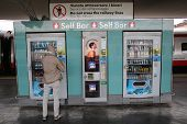 BOLOGNA, ITALY - APRIL 19, 2014: A man buys a snack from an outdoor vending machine in Bologna, Ital
