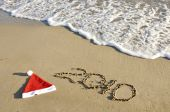 Santa Hat With New Year On The Sand With Wave.