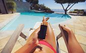 Woman Sunbathing On Deckchair With Phone