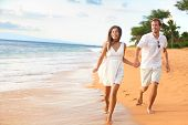 Beach couple walking on romantic travel honeymoon having fun running on vacation summer holidays rom