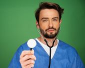Handsome young male anaesthetist or doctor holding a stethoscope up with the disk facing the camera