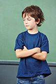 Pensive boy in elementary school thinking with his arms crossed