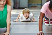 Children doing push ups in PE in elementary school