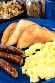 Closeup of a scrambled egg breakfast with sausage links, toast and hash brown potatoes. Vertical for