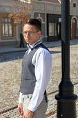 Man In Shirt And Vest With Bow Tie And Glasses, Standing Leaning Against Lamppost