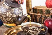 Pouring Tea From Kettle On Old Wooden Table With Fruit