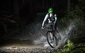 pic of freeze  - Mountain biker speeding through forest stream - JPG
