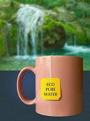Cup with yellow tea bag Eco pure water and waterfall