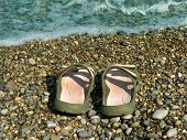 Pair of slipper on beach and wave
