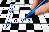 Hand filling in a crossword - family and love