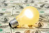 Lighting lamp on money background, business concept