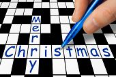 Hand filling in crossword - Merry Christmas, holiday concept