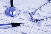 Stethoscope and pen on ecg - medical background