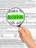 Magnifying glass in hand and word Decision - business background