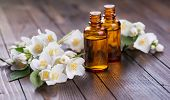 stock photo of massage oil  - Essential aroma oil with jasmine on wooden background - JPG
