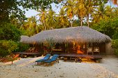 Beach bungalow at sunset - Maldives vacation background