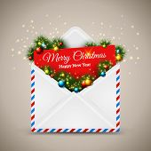 Open envelope and card Merry Christmas with fir tree branches.