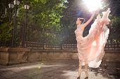 Young beautiful ballerina with pink dress dancing