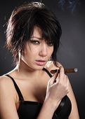 Sexy brunette woman with black bra smoking cigar