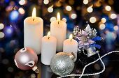 Four White Lighted Candles And Christmas Decorations On A Bokeh Background