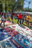 People Hugging Near Section Of Aids Quilt