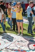 Young Woman Photographs Aids Quilt Section