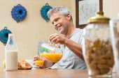 Happy Mature Man Pouring Orange Juice Into Glass For Breakfast