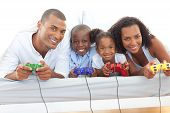 Animated Family Playing Video Game Lying Down On Bed poster