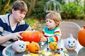 Adorable Little Child And His Father  Making Jack-o-lantern For Halloween In Autumn Garden