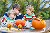 Young Father And Two Little Sons Making Jack-o-lantern For Halloween In Autumn Garden