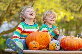 Two Little Sibling Boys Making Jack-o-lantern For Halloween In Autumn Garden